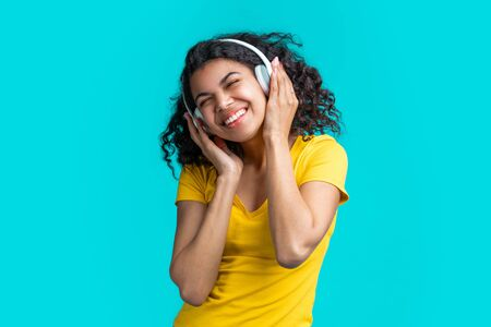 Half length portrait of casually dressed cute girl chilling, enjoying listening to music via wireless headset, dancing over bright colored blue background Imagens