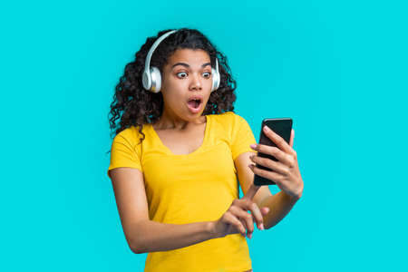 Cute african girl in wireless headset taking selfie with amazed mouth open face expression on her mobile phone Imagens