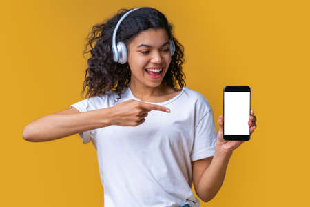 Cute smiling dark skinned girl in basic white t-shirt and wireless earphones showing blank screen of her smartphone at the camera. Mock up, copy space for your text, logo or interface. Imagens