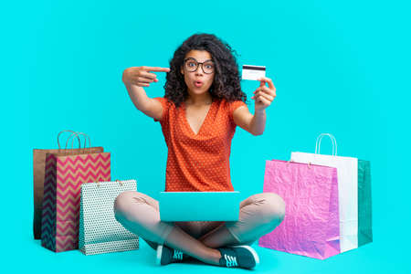 Attractive young dark skinned woman sitting with her laptop and credit card surrounded by a bunch of shopping bags making purchases online in the internet store Imagens