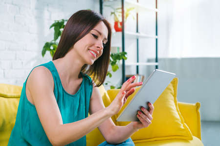 Attractive young woman with charming smile browsing applications on her laptop computer. Pretty girl making online purchases in the internet store siting at home on yellow sofa. Imagens