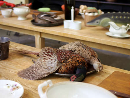Hunting trophies, pheasants lie on a platter standing on a wooden, planed table. Skilfully made fake.