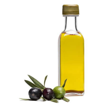 Glass bottle of  cold-pressed premium virgin olive oil and some colorful and organic olives with leaves isolated on a white background