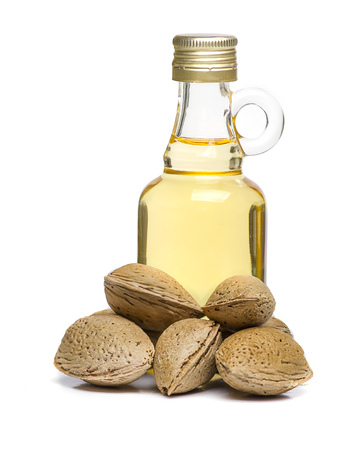 Glass bottled almond oil and some unpeeled almonds isolated on white background