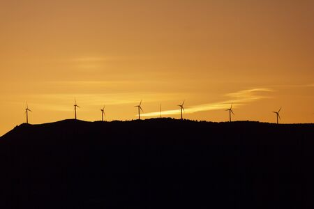 Wind turbines Silhouettes with orange sunset sky as background