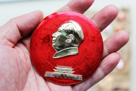 mao badge in hand