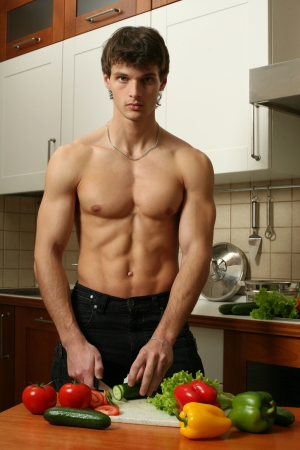 Young muscular man preparing salad at the kitchen