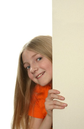 Pretty blond girl peeping over a blank billboard isolated on white photo