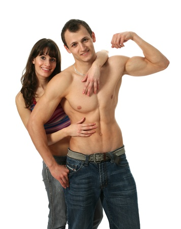 embracement: Young woman embracing a muscular boyfriend with flexing biceps isolated on white