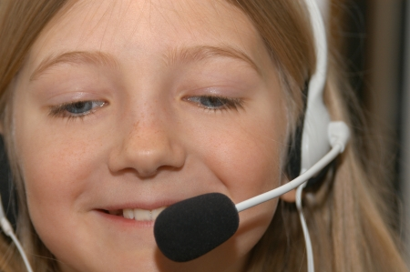Young girl learning foreigner language with a headset and a microphone photo