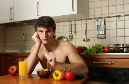 Young muscular man eating his breakfast at the kitchen photo