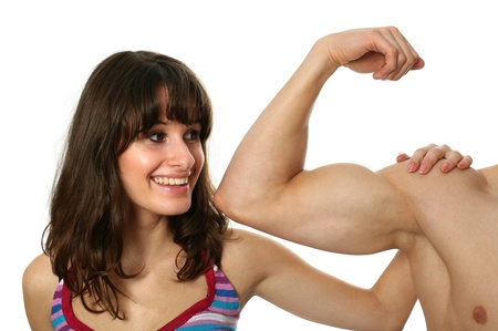 flex: Young woman examining flexing biceps of a muscular boyfriend isolated on white