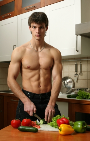 torso only: Young muscular man preparing salad at the kitchen
