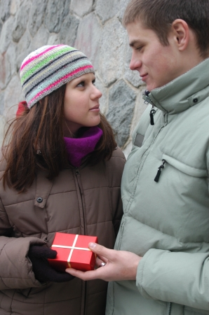 Valentines Day Gift. Young man giving a red gift box to his girlfriend photo