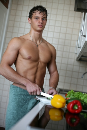 Young muscular sexy man preparing salad at the kitchen photo