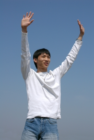 Young Asian man throwing his hands up photo