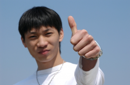 Young Asian man making a thumb up saying OK - hand in focus photo