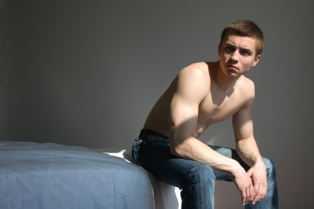 impotence: Young sexy men sitting on a bed in a bedroom