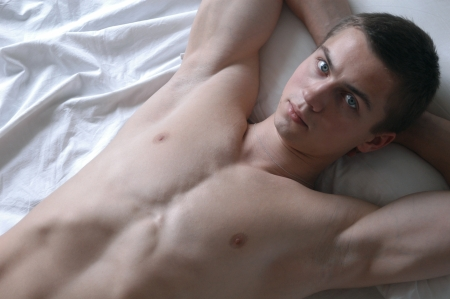 Young sexy man lying on a bed Stock Photo - 15483985
