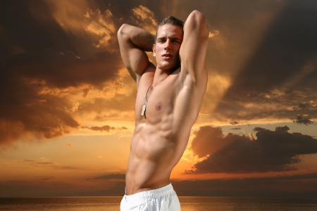 Muscular young man on the beach in the evening Stock Photo - 15531582