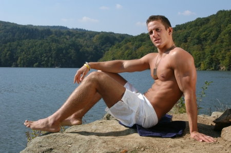 Muscular male model sitting at the beach Stock Photo