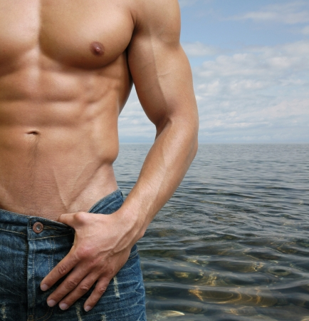 Muscular male torso on the beach Stock Photo - 15484038