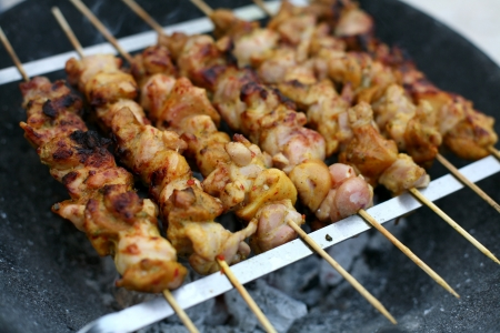 Roasting shish kebab or shashlik on skewers photo
