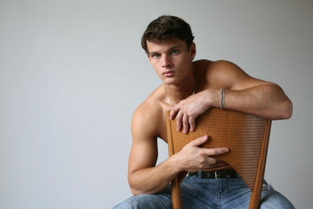 Young sexy man sitting on a chair photo
