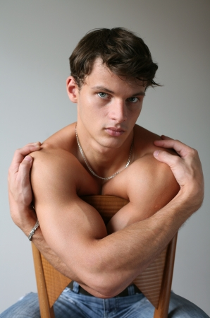 only the biceps: Young sexy man sitting on a chair