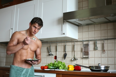 Young muscular sexy man eating his breakfast at the kitchen