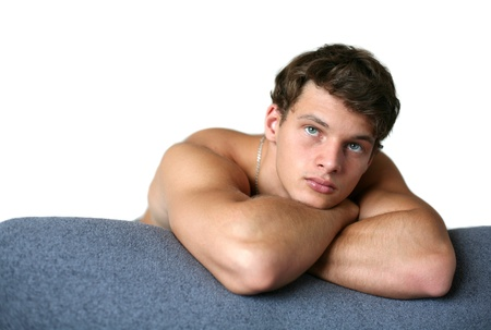 sexy muscular man: Sexy muscular man leaning on the sofa isolated on white