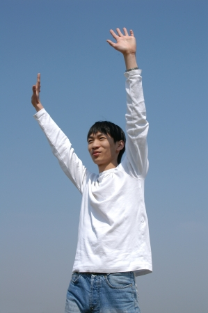 Young Asian man throwing his hands in the air photo