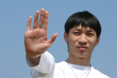 Young Asian man holding hand up saying Stop or No - palm in focus photo