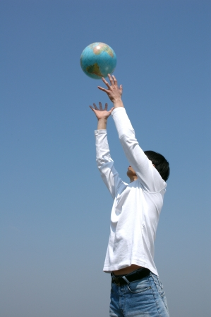 Young Asian man playing with a terrestrial globe photo