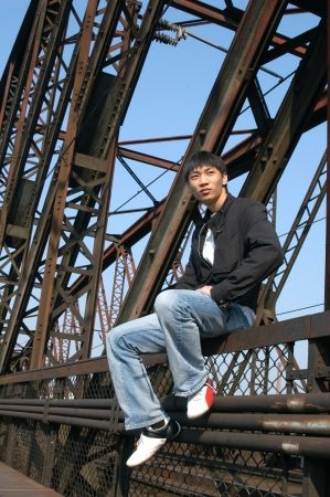 Young Asian man sitting on the railway bridge photo