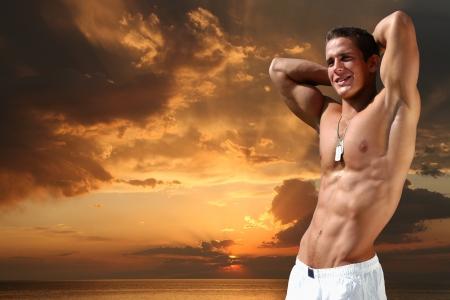 nue plage: Musculaire jeune homme sur la plage le soir