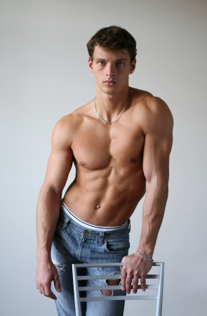 Young muscular man leaning on a chair photo