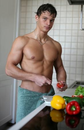 vegetable cook: Giovane uomo muscolare preparare insalata in cucina