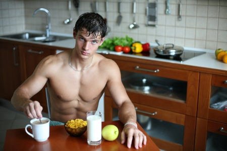only young adults: Young muscular sexy man eating his breakfast at the kitchen