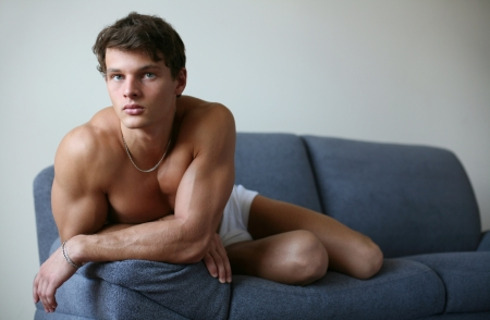Young sexy man lying on a sofa   photo