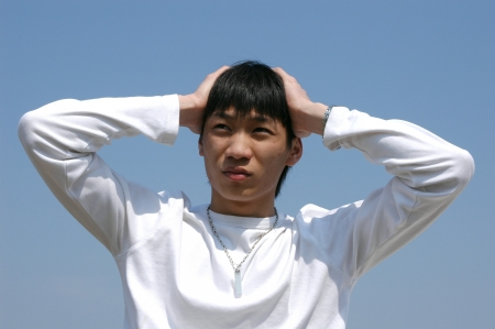 Worried young Asian man holding a head photo