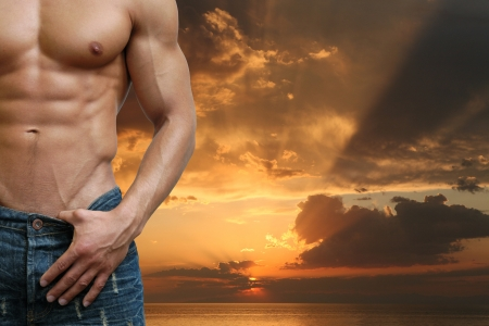 naked abs: Muscular male torso on the beach in the evening