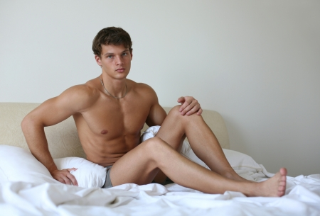 nude in bed: Young sexy man lying on a bed