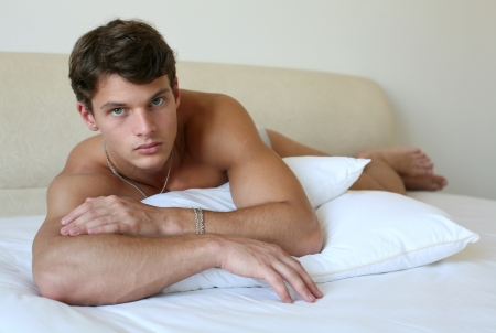 naked man: Sexy muscular man lying on the bed Stock Photo