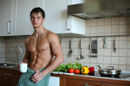 torso only: Young muscular sexy man eating his breakfast at the kitchen