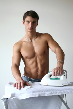 Young muscular man ironing a shirt