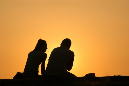 Silhouetted loving couple at sunset photo