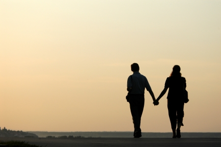 Silhouetted loving couple walking at sunset photo