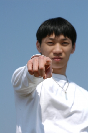 Lets Do It! Young Asian man pointing forward - hand in focus photo