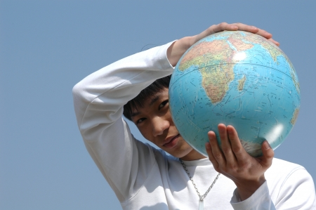 terrestrial: Young Asian man holding a terrestrial globe